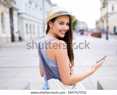 Woman using mobile phone on city street - stock photo