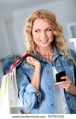 Woman using mobile phone while shopping - stock photo