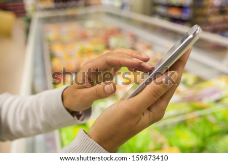 Woman using mobile phone while shopping in supermarket, frozen department store - stock photo