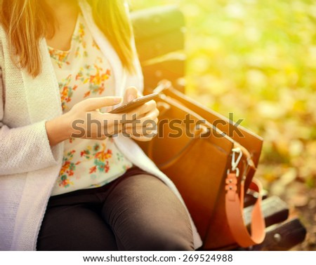 Woman using mobile smart phone in the park - stock photo