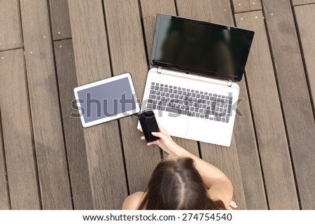 Woman using multiple devices phone laptop and tablet lying in a wood bench in a park - stock photo