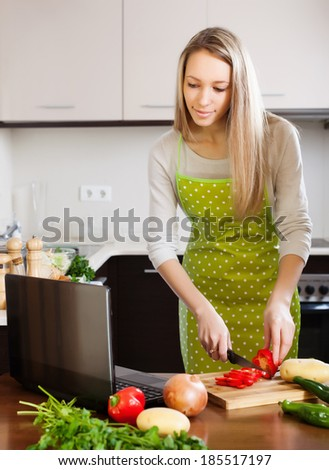 woman using notebook during cooking vegetables at home