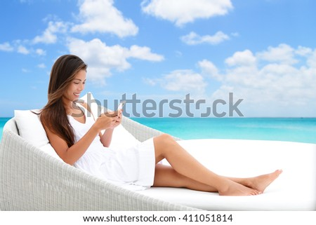 Woman using phone app relaxing on sun bed on outdoor terrace. Home living outside patio furniture Asian girl on smartphone lying on beach lounger in white dress with ocean background enjoying summer.  - stock photo