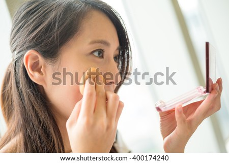 Woman using powder to touch up on her face - stock photo