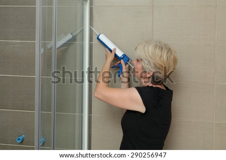 Woman using silicone cartridge for fixing aluminum batten of shower cabin