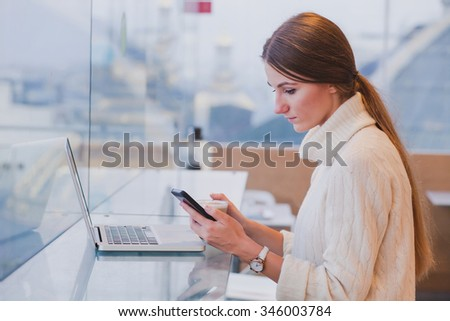 woman using smart phone in modern cafe interior, mobile application, checking email  - stock photo