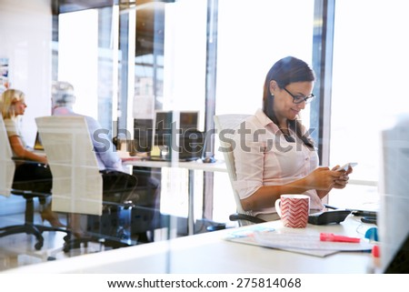 Woman using smart phone,phone at her desk in an office - stock photo