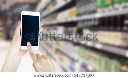 Woman using smart phone while shopping in supermarket