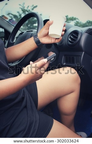 Woman using smart phone with coffee paper cup in the car.