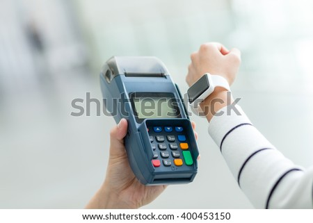 Woman using smart watch to pay by NFC technology - stock photo