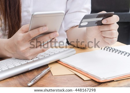 woman using smartphone and computer to online shopping and pay by credit card, Low light, selective focus on hand, can be used for e-commerce, business, technology and internet concept - stock photo