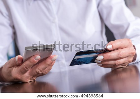Woman using smartphone and credit card for online payment