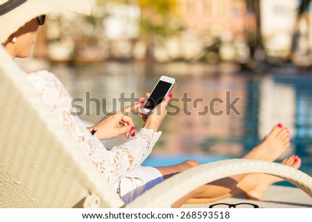 Woman using smartphone by the pool - stock photo