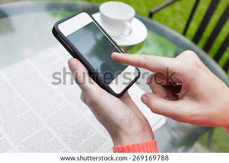 Woman using smartphone in the cafe - stock photo