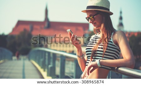 Woman using smartphone in the European city. Hipster girl browsing Internet on a phone, texting and communicating outdoors. Travel concept - stock photo
