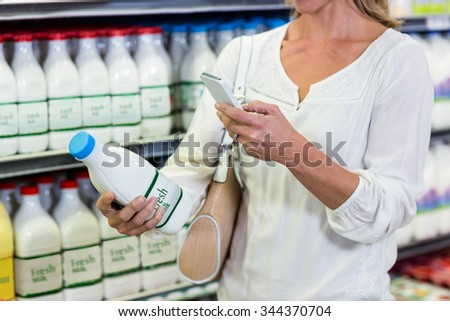 Woman using smartphone while holding milk bottle at the supermarket