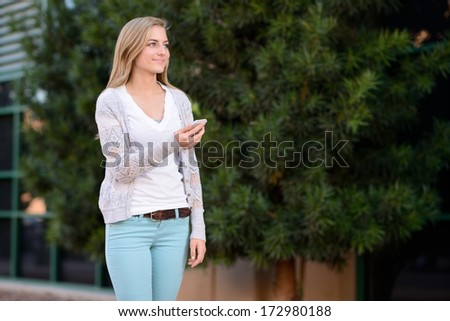 Woman using smartphone. Young girl walking outisde with a cellphone.