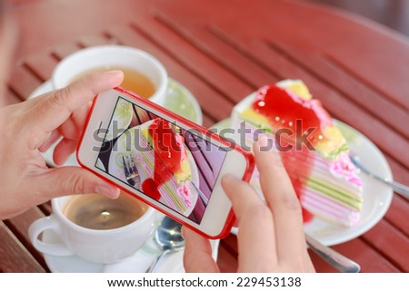 Woman using smartphones to take photos of food - stock photo