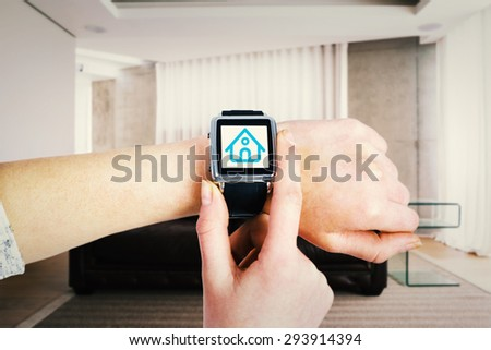 Woman using smartwatch against brown leather couch in a modern living room - stock photo