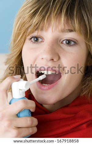 Woman Using Spray In Mouth