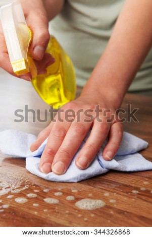 Woman Using Spray To Clean Wooden Surface