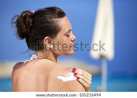 Woman using suncream - stock photo