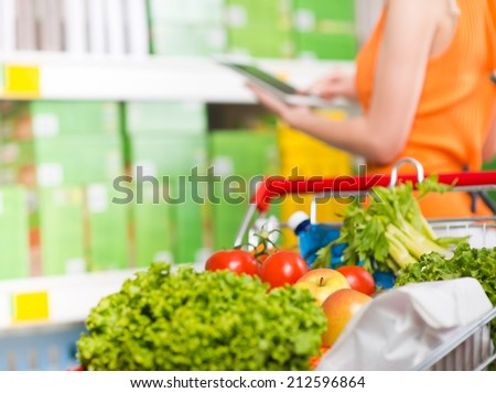 Woman using tablet at store with grocery on foreground. - stock photo