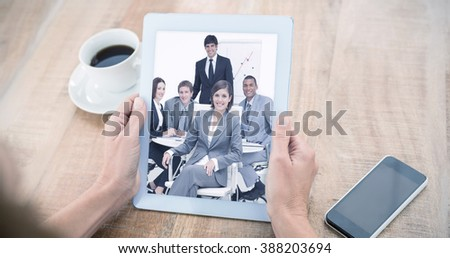 Woman using tablet computer at table against happy business group having a meeting - stock photo