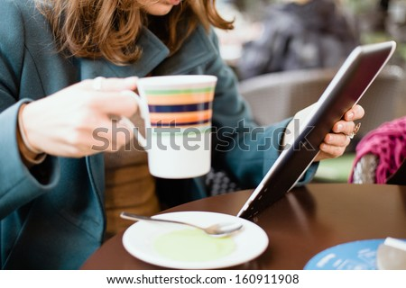 Woman using tablet computer in cafe drinking coffee - stock photo