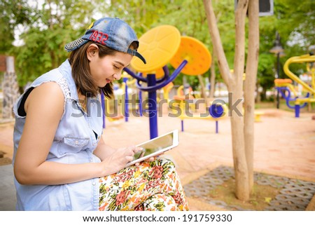 Woman using tablet computer in public park - stock photo