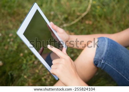 Woman using tablet in park on a sunny day
