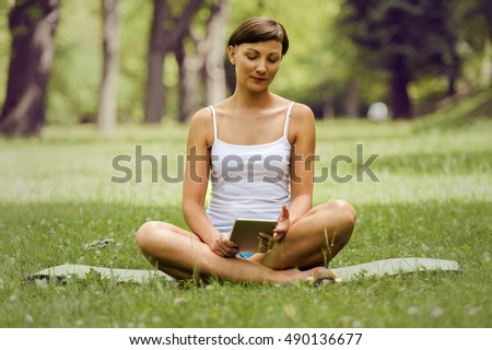 Woman using tablet on the grass.