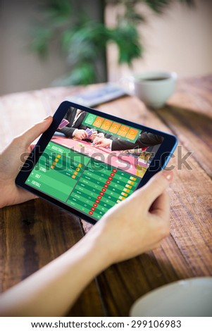 Woman using tablet pc against gambling app screen