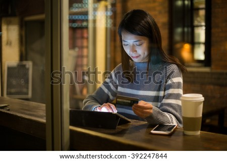 Woman using tablet pc for online shopping at cafe