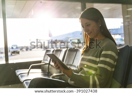 Woman using tablet pc in departure hall of airport - stock photo