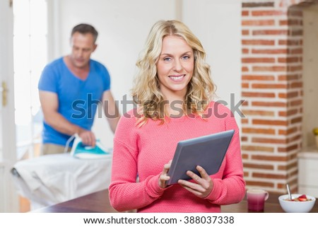 Woman using tablet while husband using iron in the living room