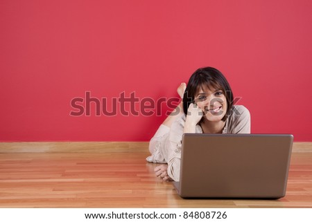 Woman using the laptop computer at her house floor, next to a red wall (selective focus) - stock photo