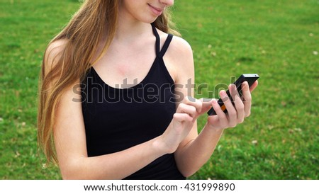Woman using touchscreen phone outdoors in city park.