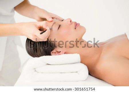 Woman using tweezers on patient eyebrow at the health spa - stock photo