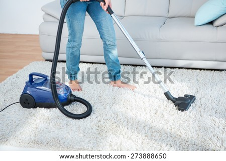 Woman using vacuum cleaner on carpet at home in the living room - stock photo