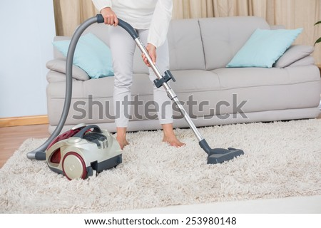 Woman using vacuum cleaner on rug at home in the living room - stock photo