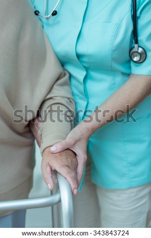 Woman using walking frame assisted by doctor - stock photo