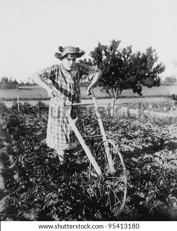Woman using walking plow in garden - stock photo