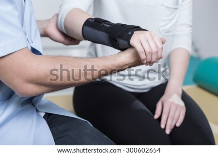 Woman using wrist immobiliser after hand's injury - stock photo