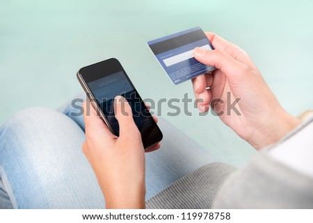 Woman verifies account balance on smartphone with mobile banking application. - stock photo