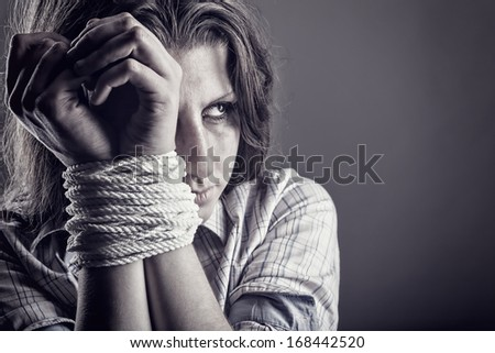 Woman victim of domestic violence and abuse on a dark background - stock photo