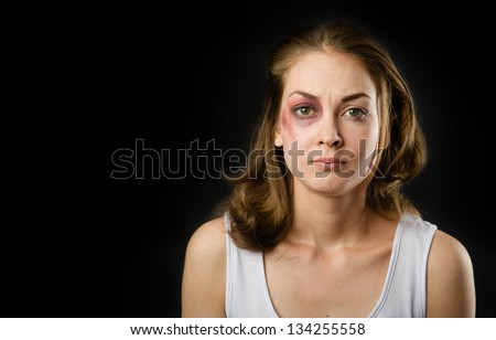 woman victim of domestic violence and abuse. on dark background - stock photo