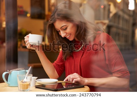 Woman Viewed Through Window Of Caf�¢?? Using Digital Tablet - stock photo