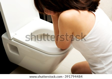 Woman vomiting in toilet. - stock photo