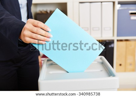 Woman voting with ballot paper on box during election - stock photo